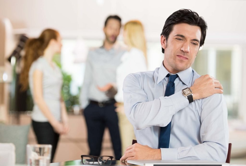 Portrait of a businessman at work suffering from shoulder pain. Portrait of stressed businessman holding shoulder and stretching after work. Mature businessman tired and stressed after working for long.
